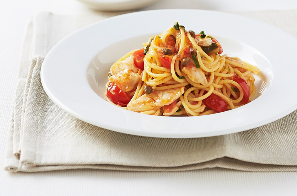 White bowl of spaghetti with fish, capers and tomato served on a linen napkin