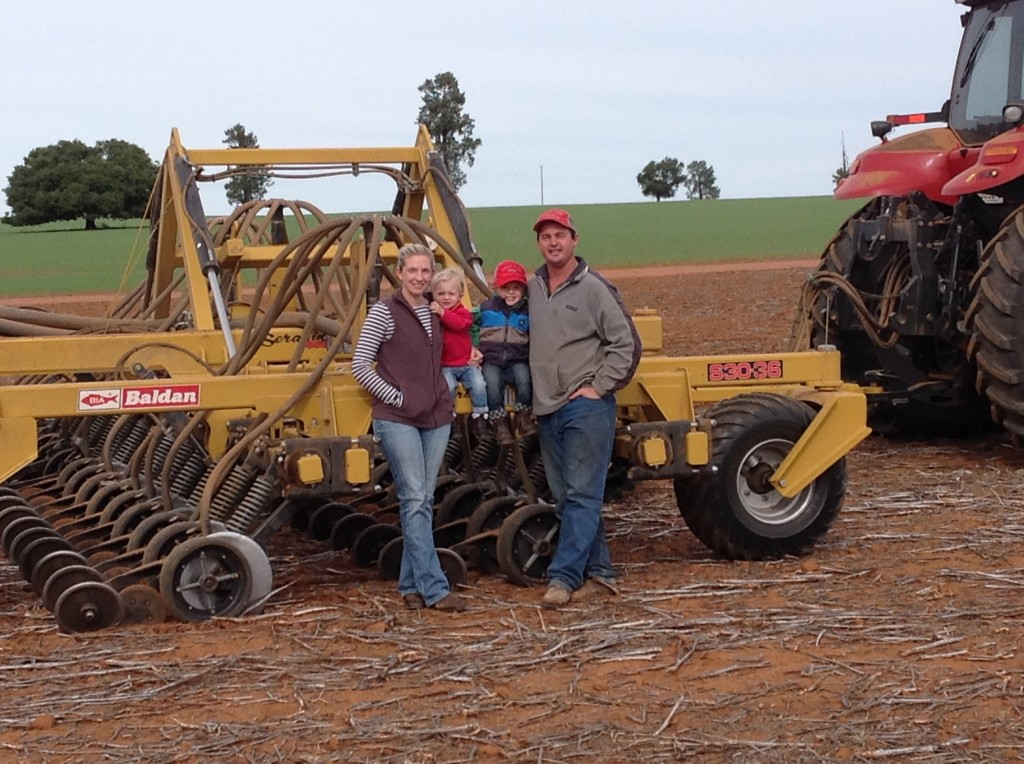 Family of four standing in front of machine on a wheat farm.