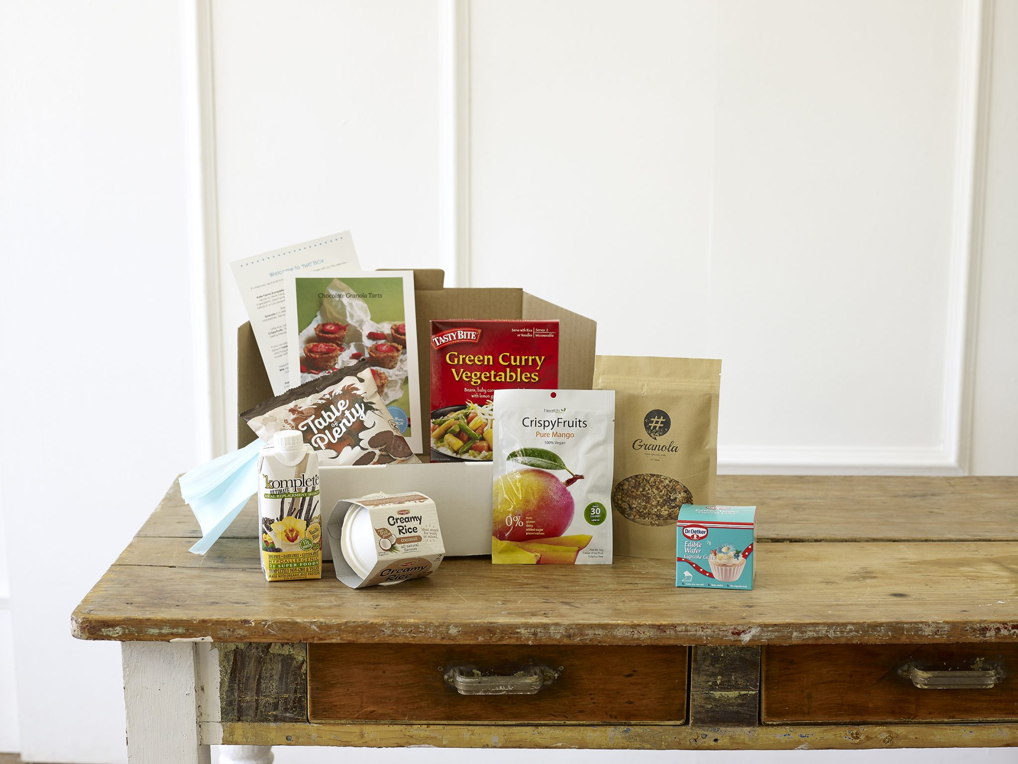A selection of gluten-free product samples including protein drink, rice crackers, rice pudding, vegetable green curry and gluten-free granola.
