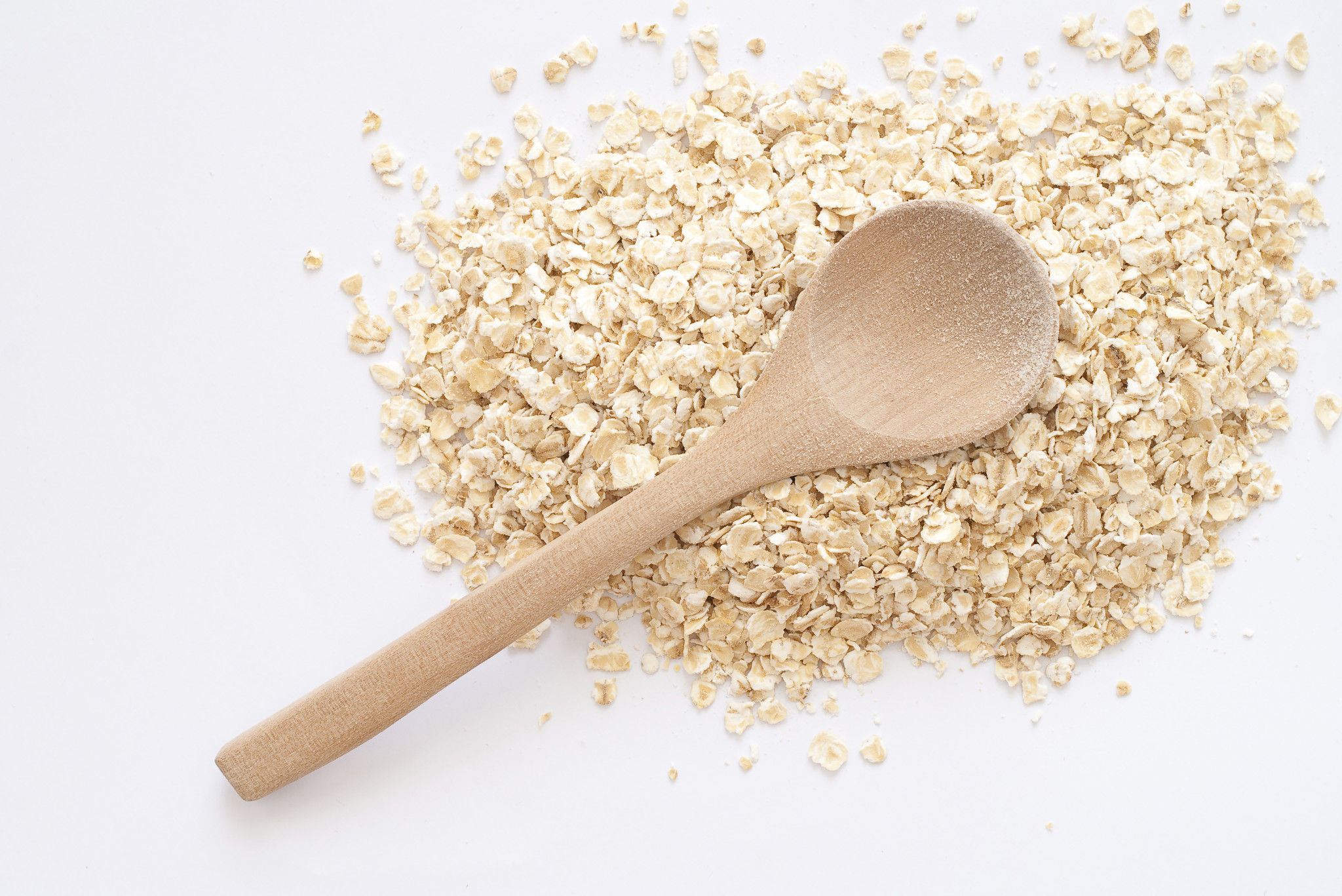 A large pile of oats with a wooden spoon