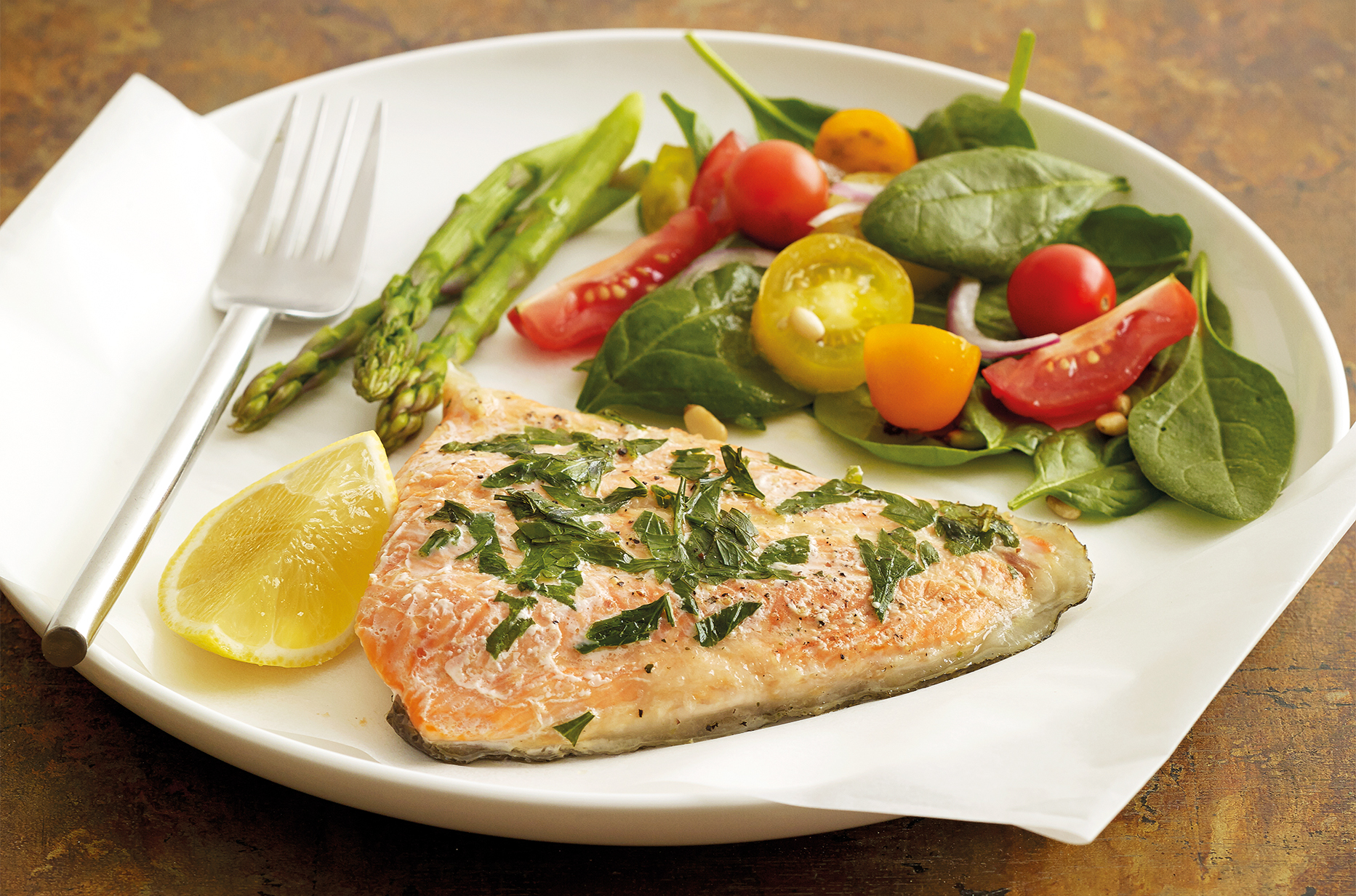 Large white dinner plate with baked salmon topped with herbs and lemon, salad and asparagus