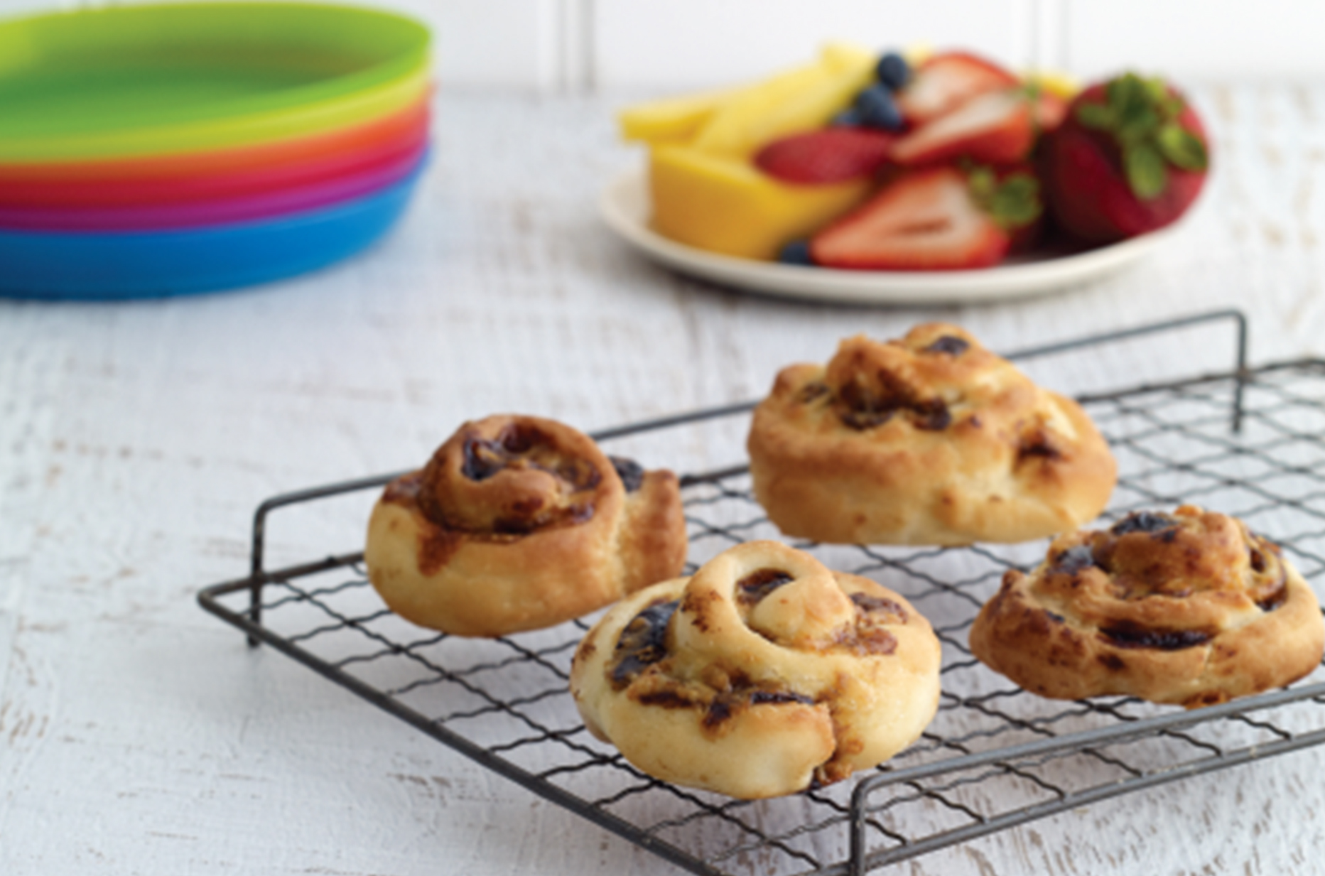 Baked savoury scrolls cooling on a wire-rack with a stack of colourful plates and chopped fruit