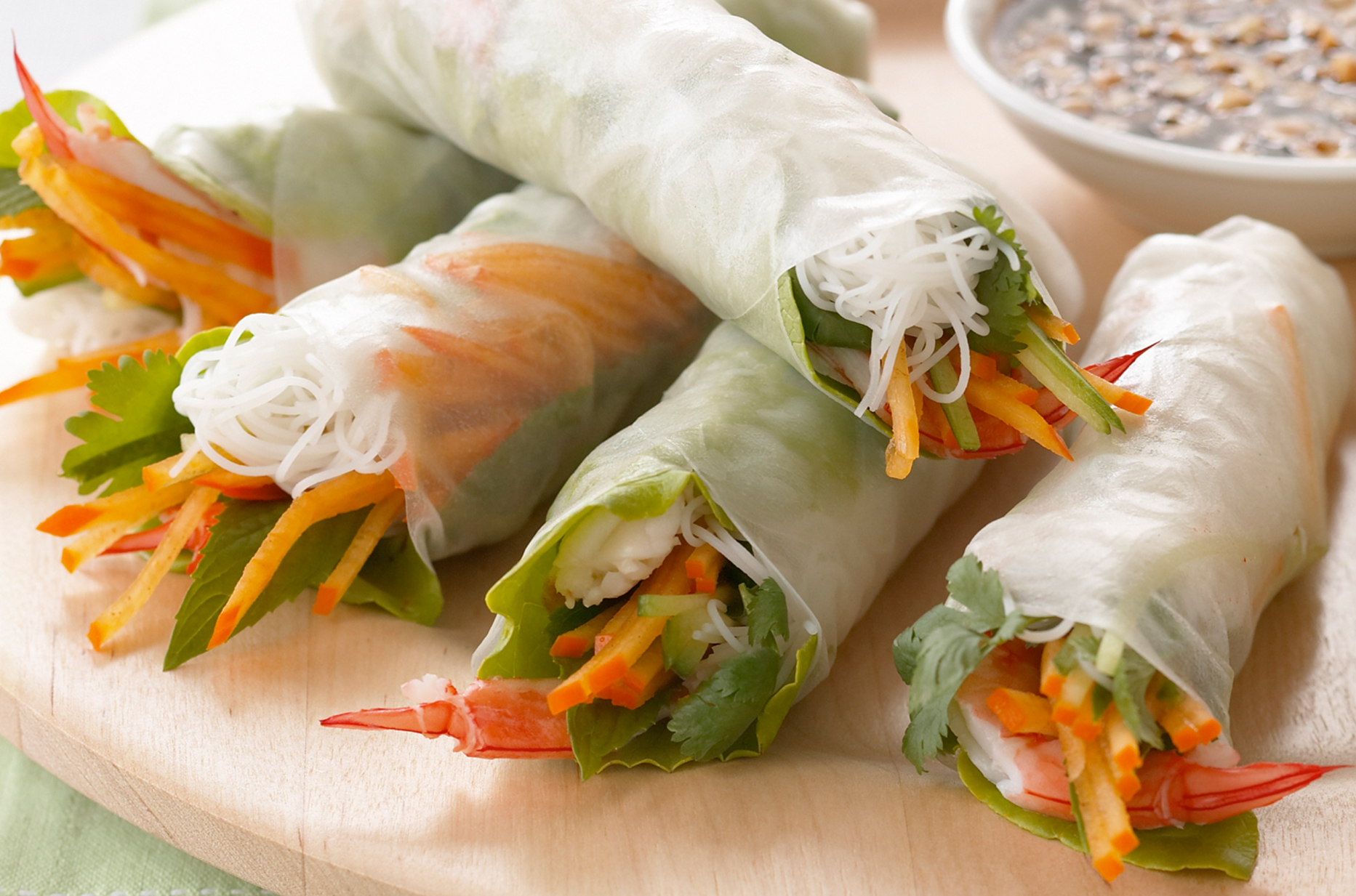 A wooden platter of rice paper rolls filled with persimon, prawns and herbs with dipping sauce