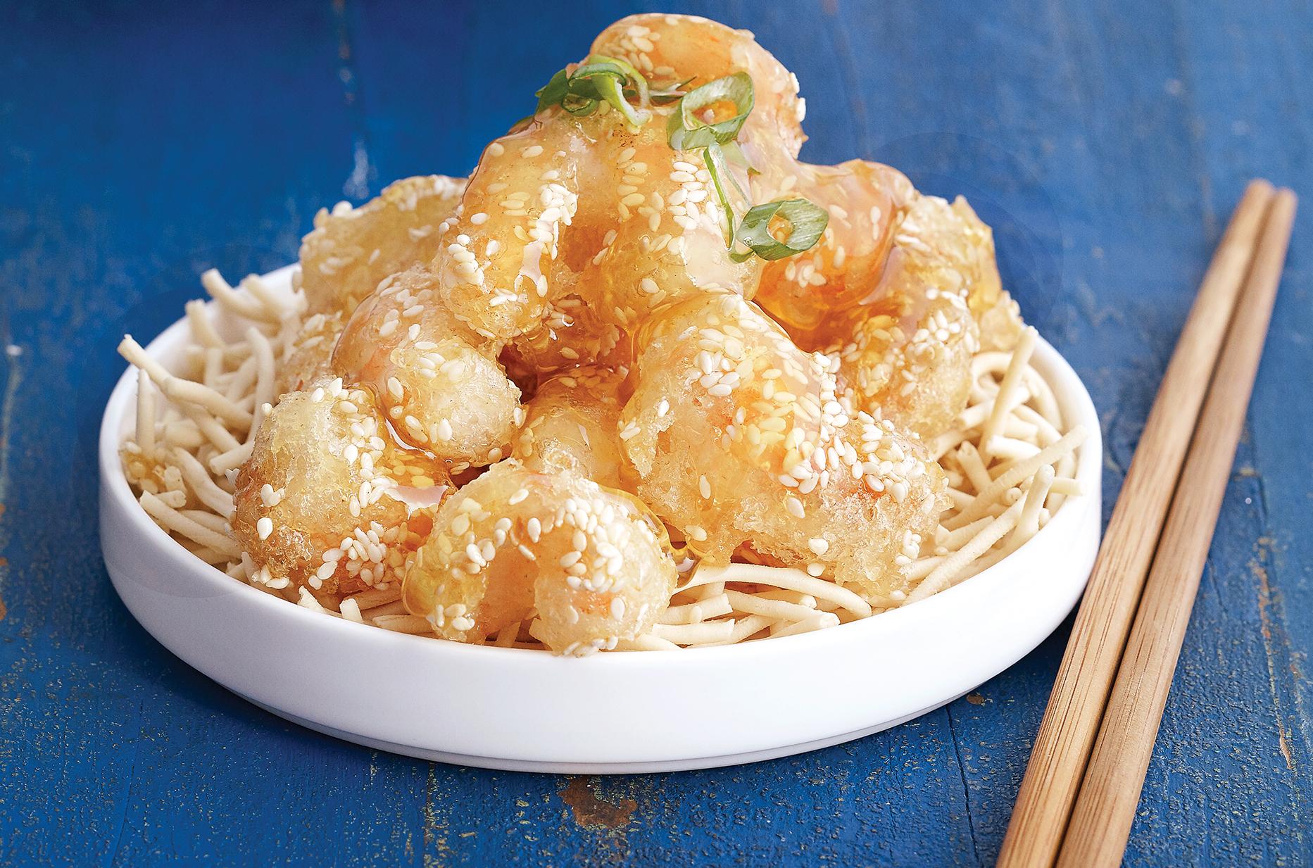 A platter of crispy gluten-free honey prawns sitting on crispy rice noodles with chopsticks on a blue board