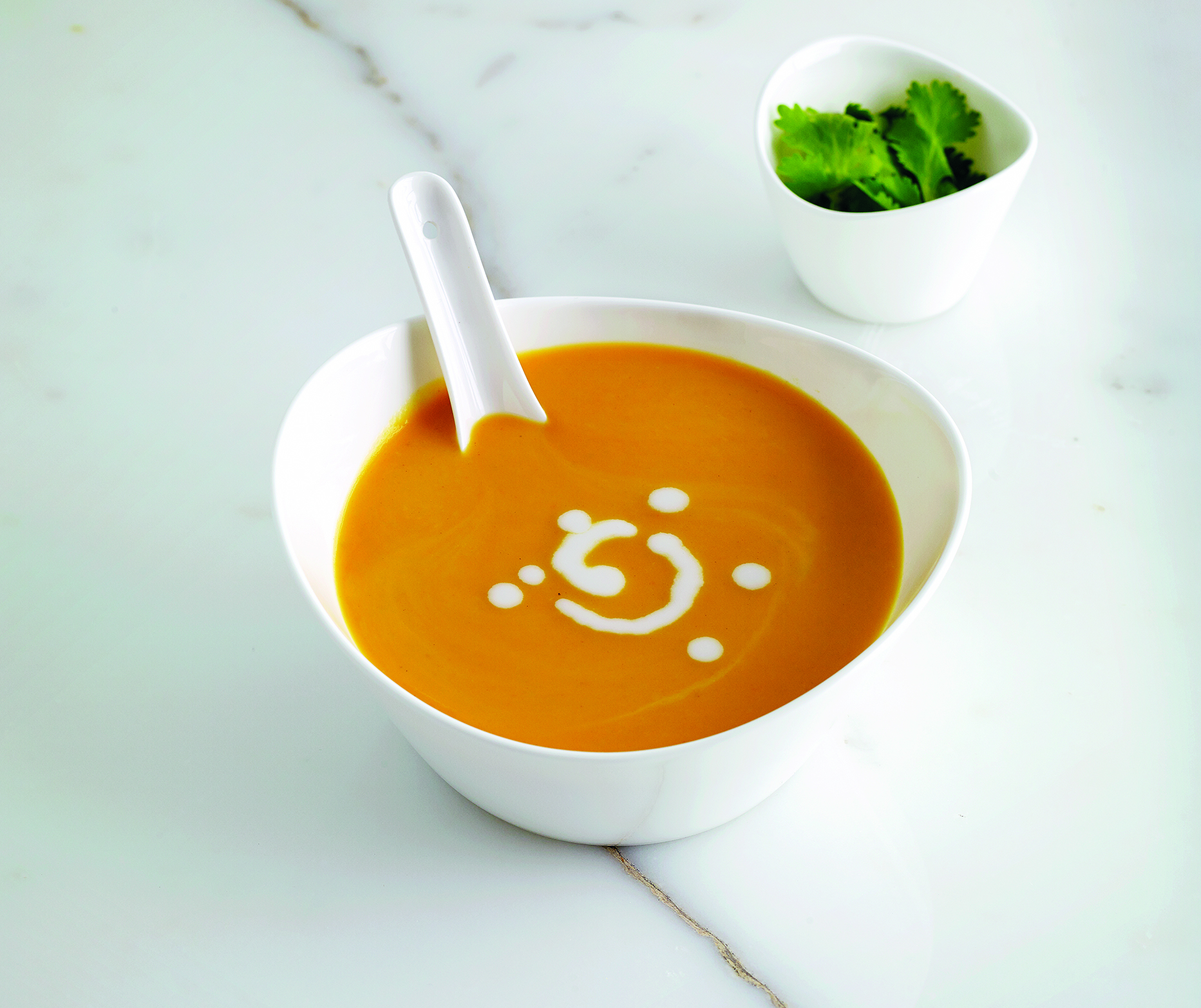 A white bowl filled with orange sweet potato soup sitting on a marble bench with a small bowl of coriander leaves
