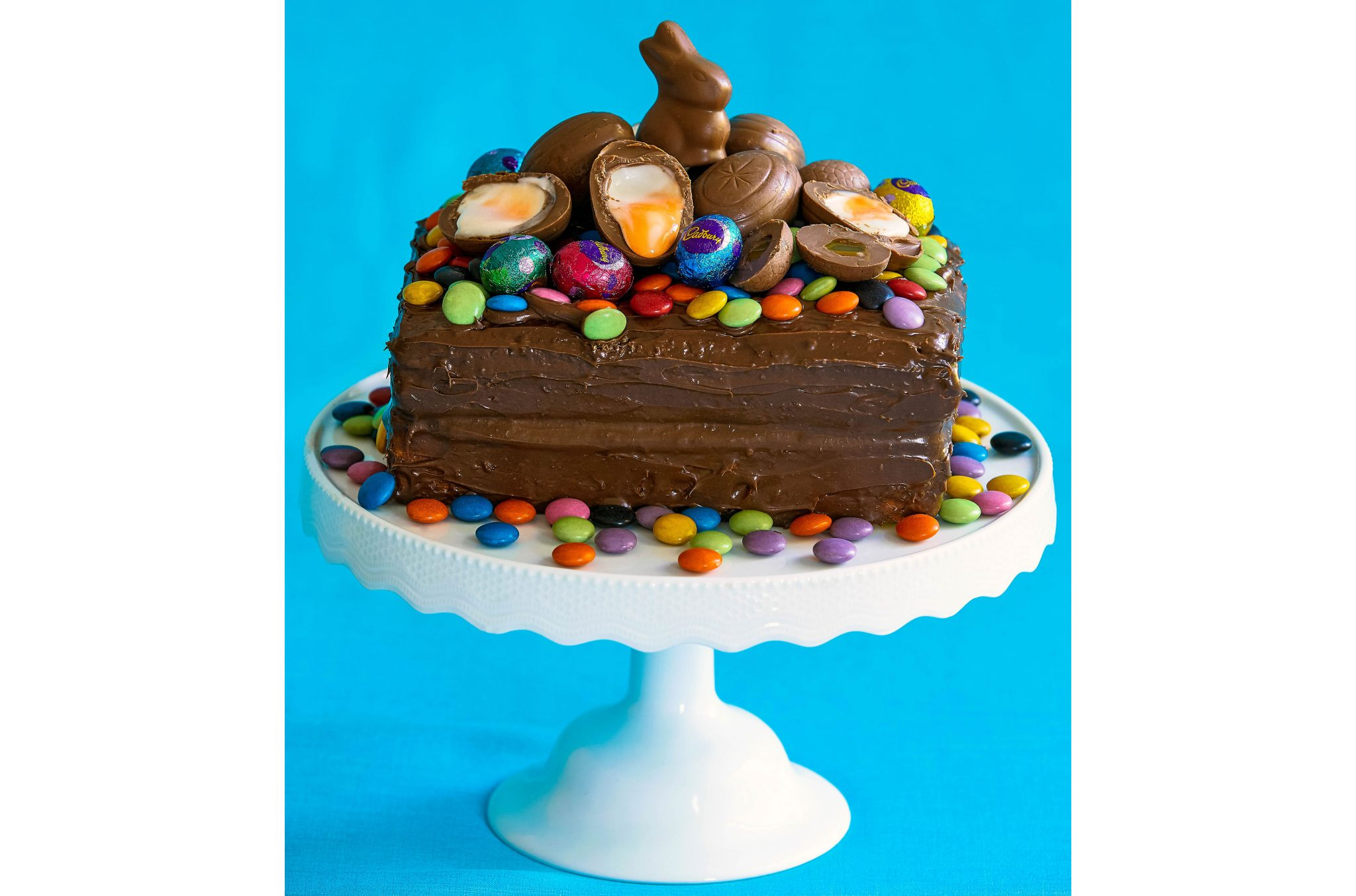 Decadent gluten-free chocolate cake on white cake stand with Easter eggs.