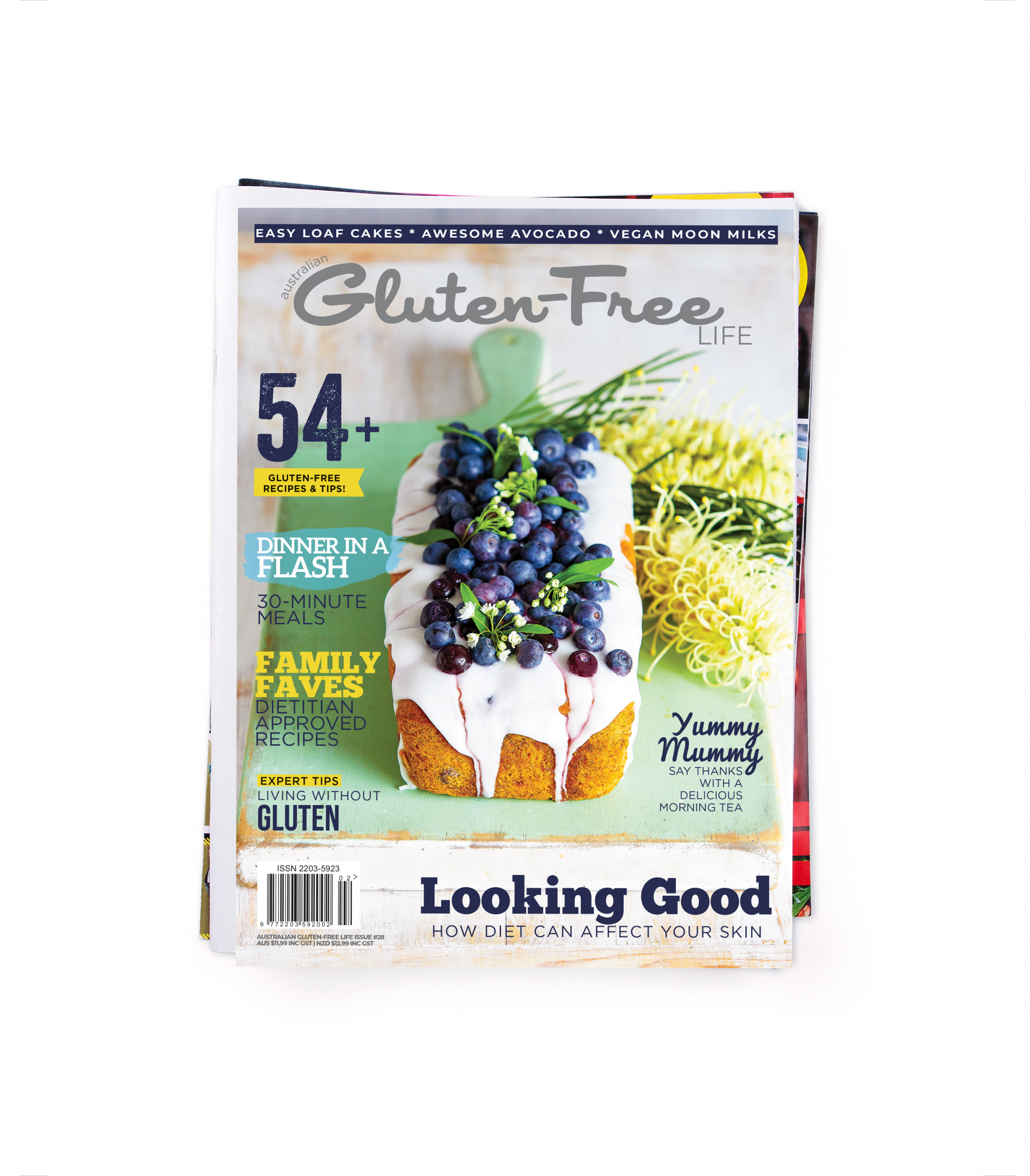 Gluten-Free Magazine with blueberry banana cake sitting on a green board with yellow flowers.