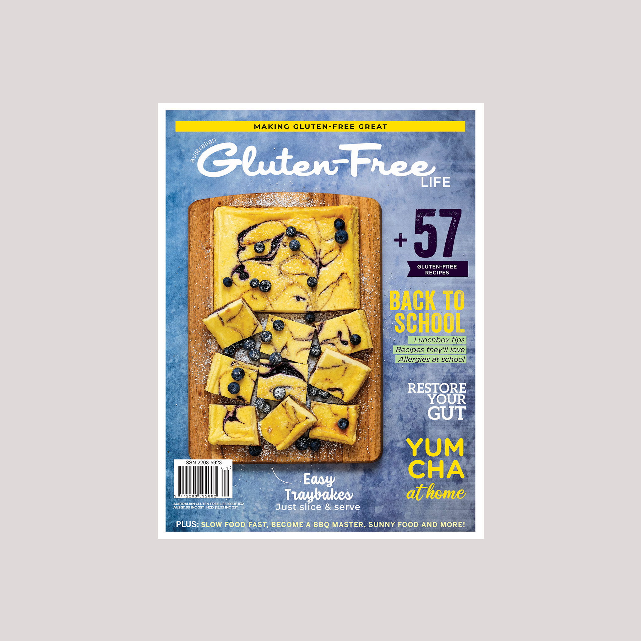 Gluten-free magazine cover with a sliced blueberry cheesecake slice on a wooden board and blue background. Yum Cha recipes, lunchbox tips, gut health and more inside.
