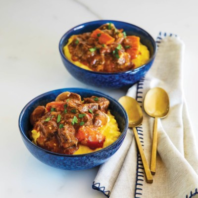 Blue bowls with slow cooker beef stew served on cheesy polenta