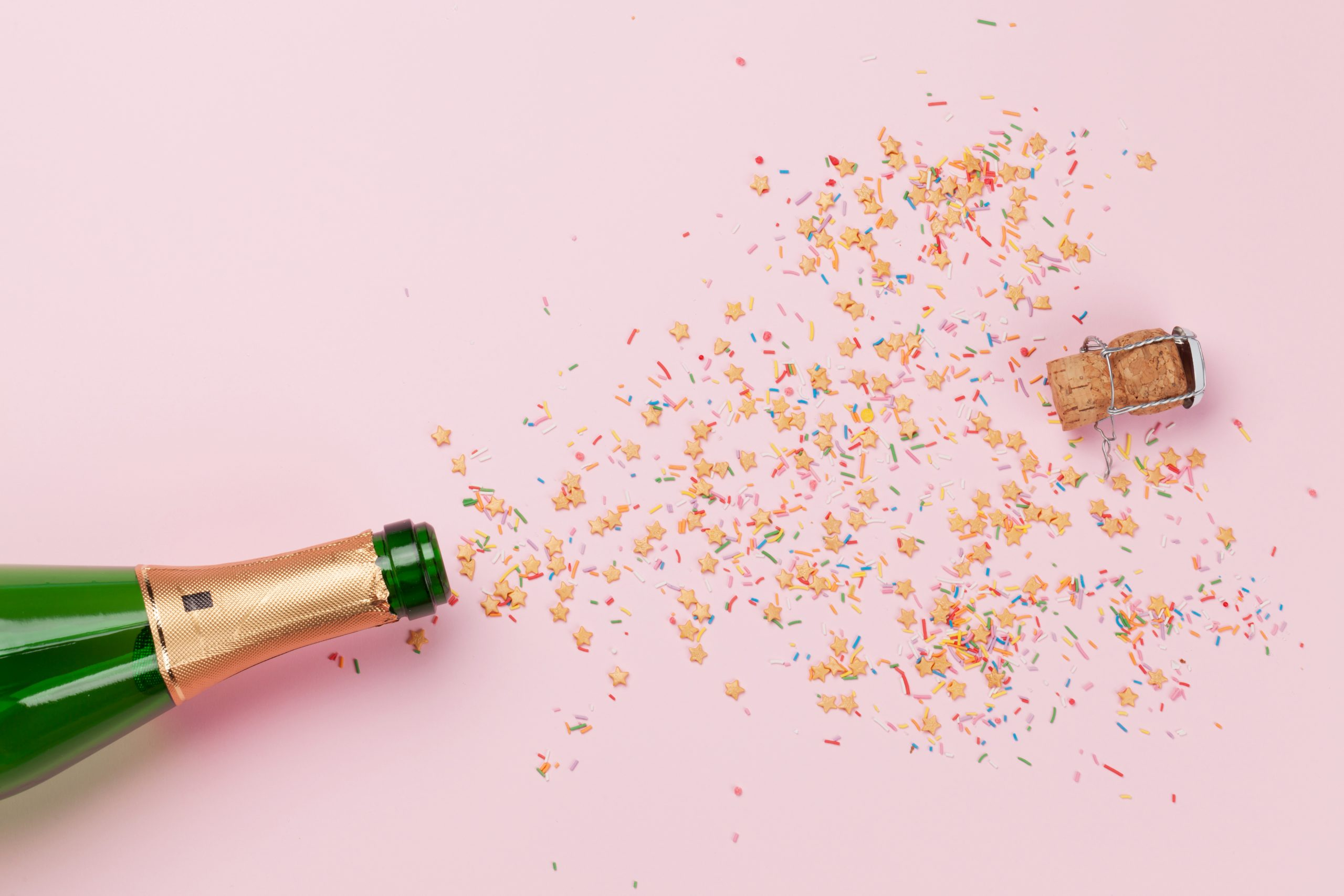 Here's Cheers - gluten-free alcohol guide champagne bottle popping with confetti on pink background