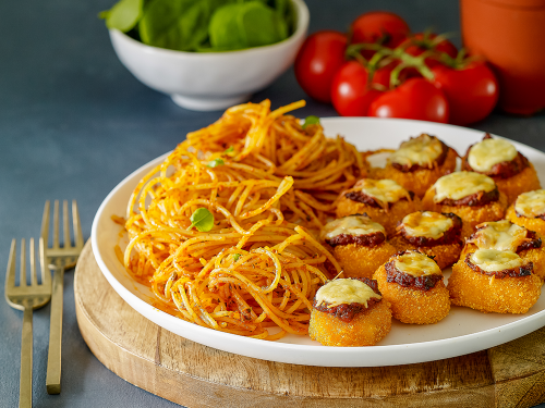 gluten-free chicken nugget parmigiana and gluten-free spaghetti on a white plate sitting on a board.